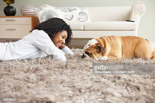 black woman laying on floor with dog - rug stock pictures, royalty-free photos & images