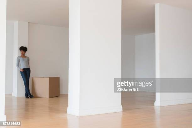 Black woman leaning on pillar in empty apartment