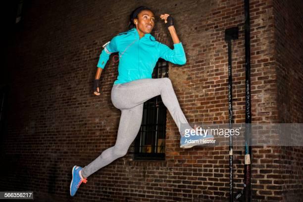Black woman leaping near brick wall at night