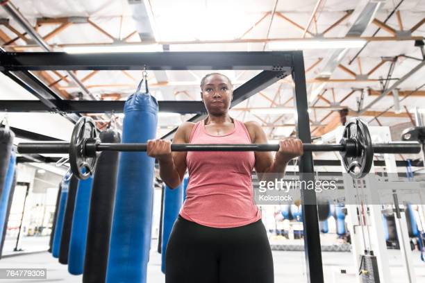 Black woman lifting barbell in gymnasium