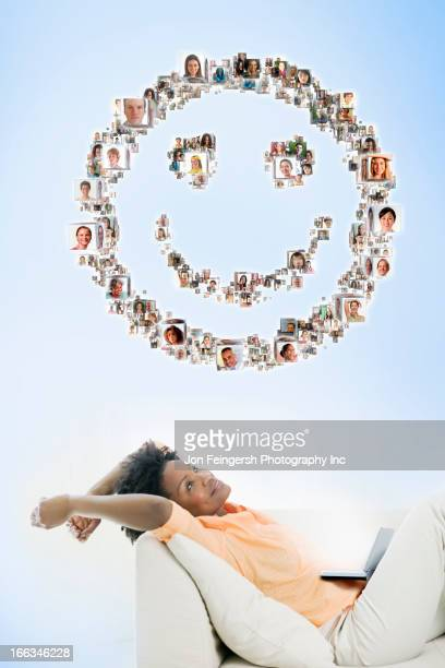 Black woman looking at smiley face made up of pictures