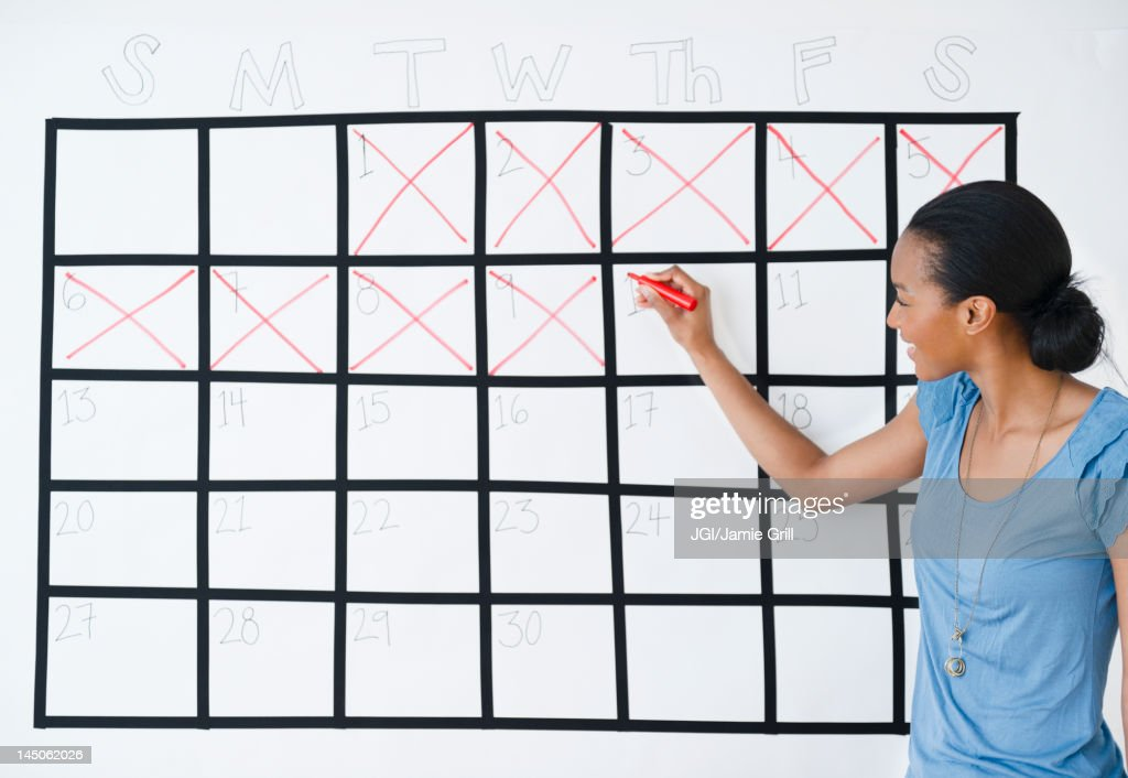 Black woman marking the days off calendar : Stock Photo