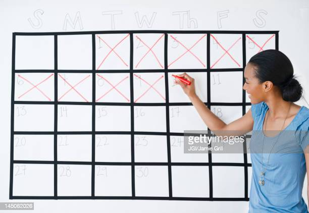 Black woman marking the days off calendar