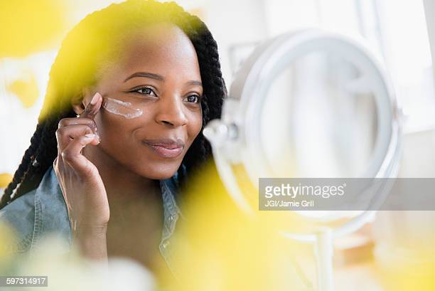 Black woman moisturizing her face