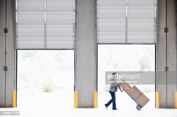 black woman moving boxes in empty warehouse - loading dock stock pictures, royalty-free photos & images