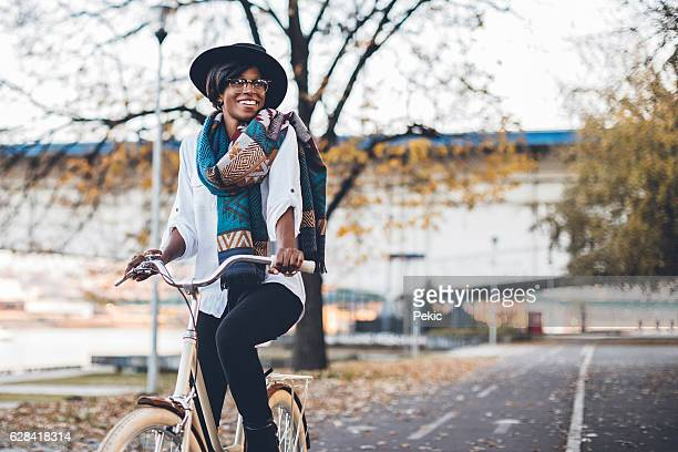 Black woman on bicycle in park