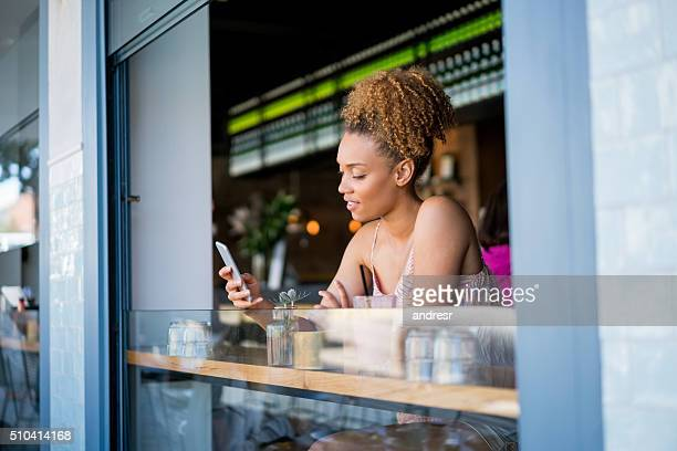 Black woman on her phone at a cafe