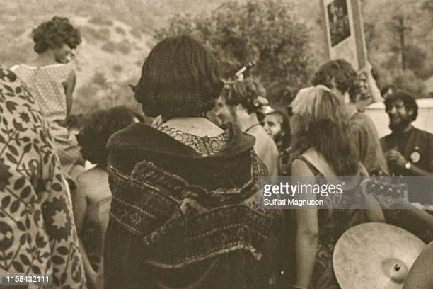 Black woman on man's shoulders smiling at those who are enjoying her spontaneous way to see the band, some with long hair and beards, and printed...