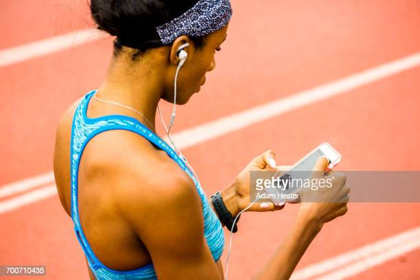 black woman on track listening to cell phone with earbuds - オリンピック選手 ストックフォトと画像