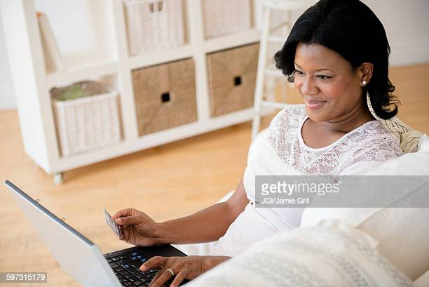 Black woman paying bills on laptop