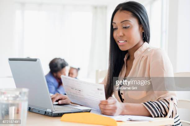 black woman paying bills using laptop - grandma invoice stock pictures, royalty-free photos & images