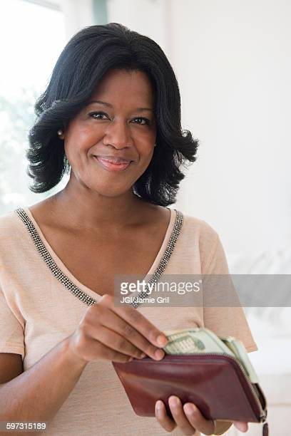 Black woman paying with cash from wallet