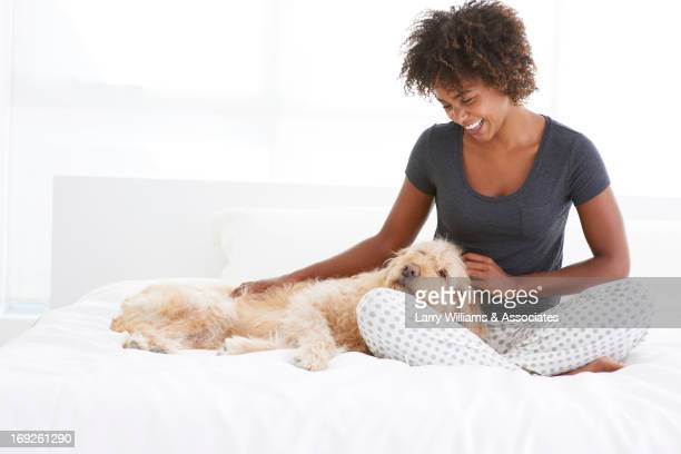 Black woman petting dog on bed