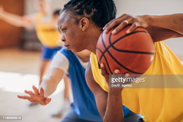 black woman playing basketball indoors - women's basketball stock pictures, royalty-free photos & images