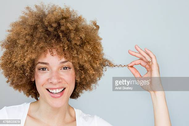 black woman playing with hair - afro frisur stock-fotos und bilder