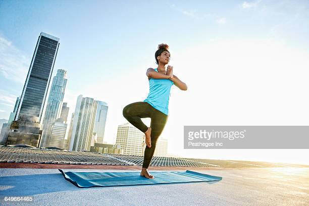black woman practicing yoga on urban rooftop - standing on one leg stock pictures, royalty-free photos & images