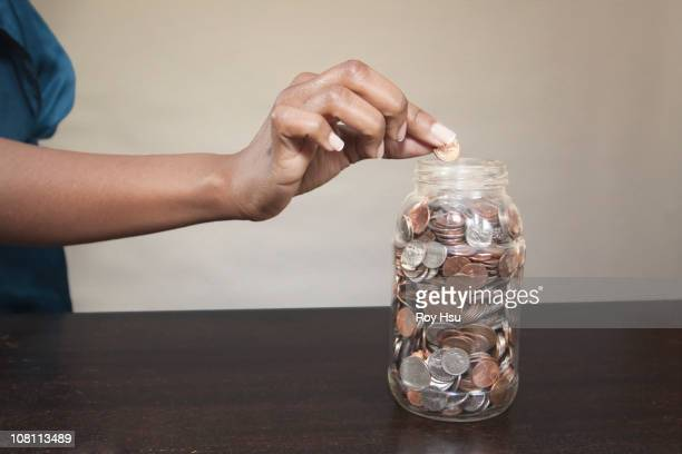 Black woman putting coin into jar