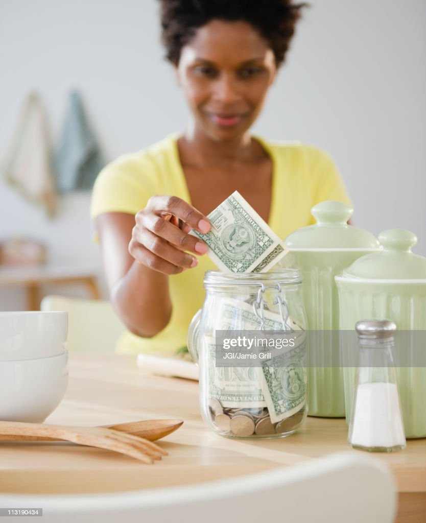 Black woman putting money in jar : Stock Photo