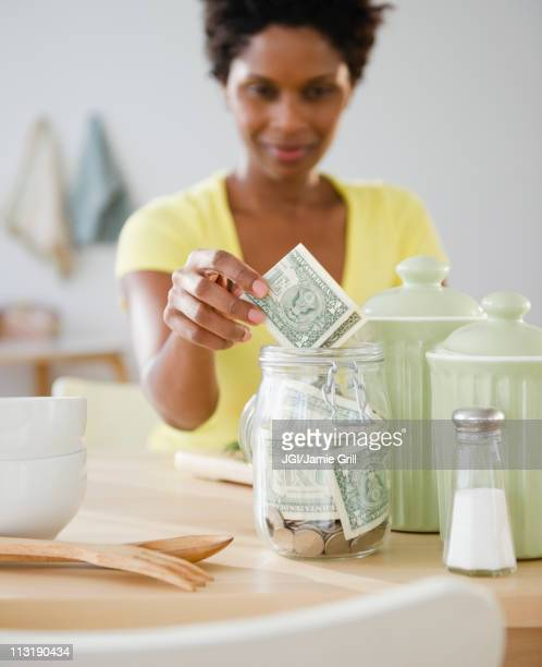 black woman putting money in jar - 40 44 jaar stock pictures, royalty-free photos & images