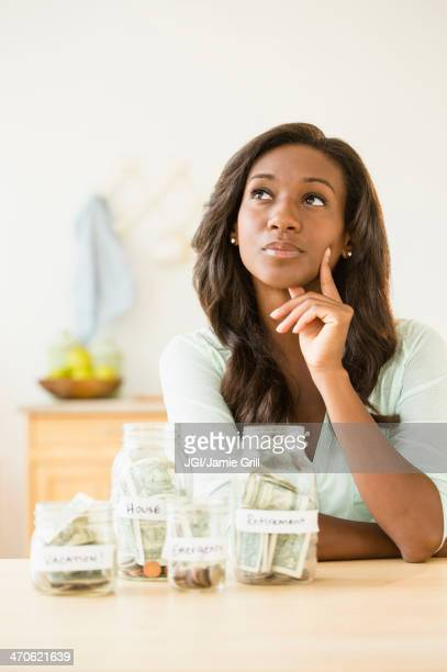 Black woman putting money into savings jars