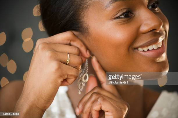 black woman putting on earring - ohrring stock-fotos und bilder