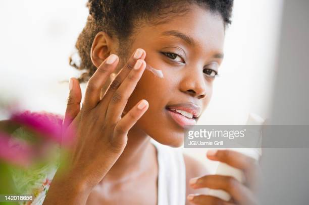 black woman putting on face lotion - sunscreen stock photos and pictures