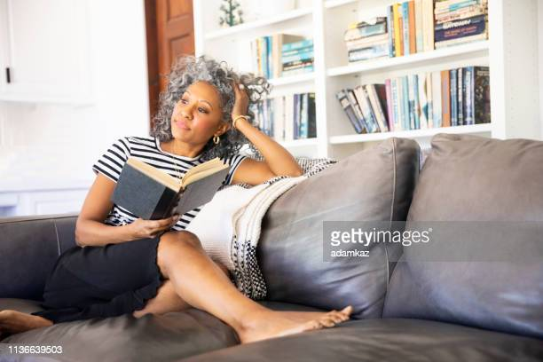 Black Woman Reading a book in her library at home