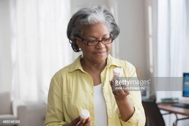 black woman reading prescription bottles - pill bottle stock pictures, royalty-free photos & images