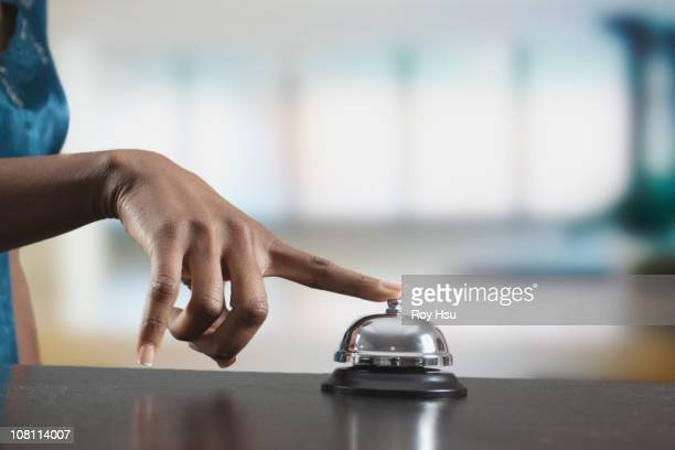 black woman ringing reception desk bell - bell stock pictures, royalty-free photos & images