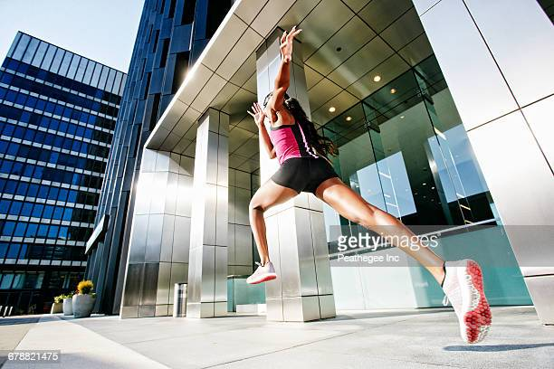 Black woman running and jumping on city sidewalk