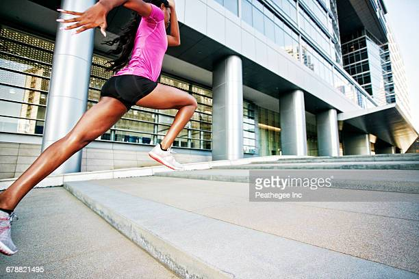 Black woman running and jumping on city staircase