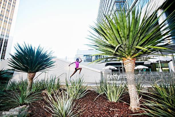 Black woman running and jumping on sidewalk near trees