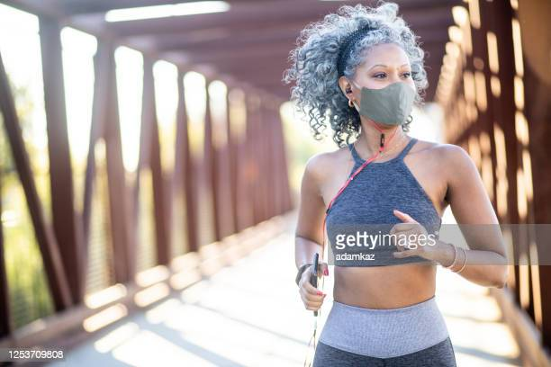 a black woman running on a bridge - adamkaz stock pictures, royalty-free photos & images
