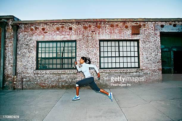 Black woman running on city street