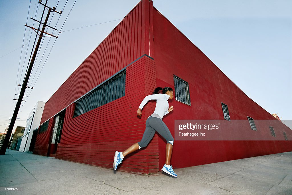Black woman running on city street : Stock Photo