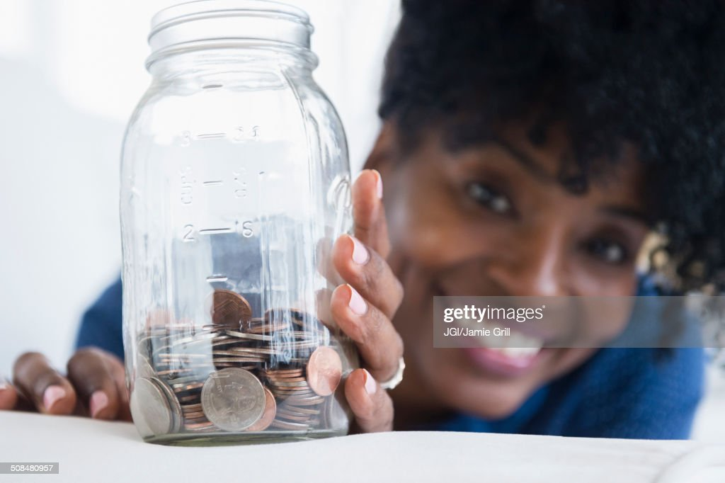 Black woman saving coins in jar : Stock Photo
