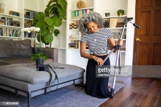 Black Woman Setting up Tripod and Camera