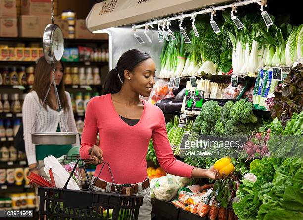 black woman shopping for fresh vegetables - produce aisle stock photos and pictures