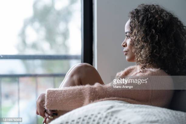 black woman sitting in the living room of her house looking away very shaken by her problems - post traumatic stress disorder stock pictures, royalty-free photos & images