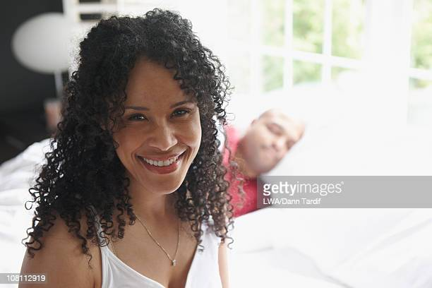 black woman sitting on bed with sleeping husband - cabello largo fotografías e imágenes de stock