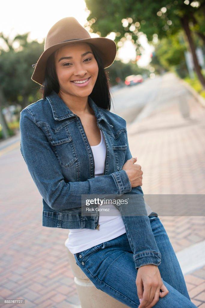 Black woman sitting on pillar : Foto stock
