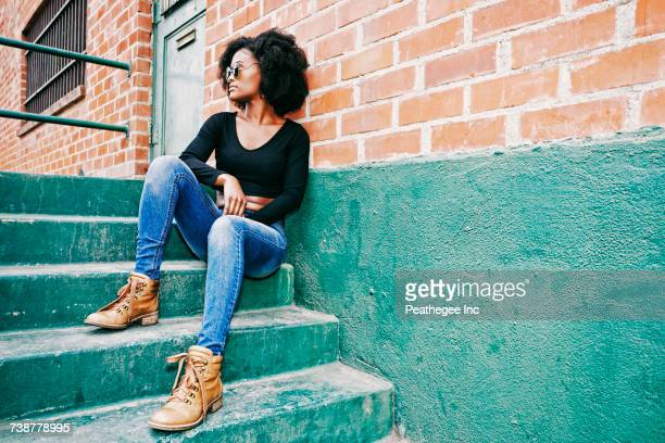 black woman sitting on staircase outdoors - black shoe stock pictures, royalty-free photos & images