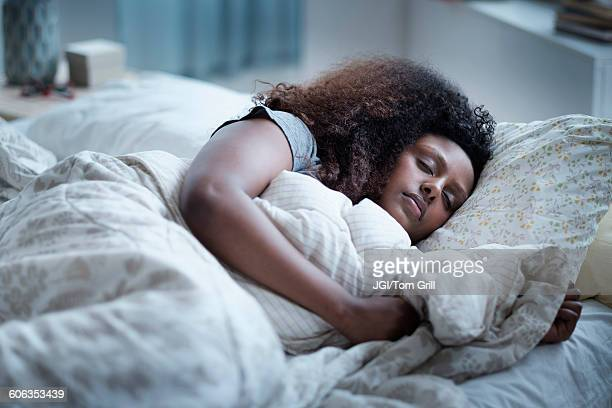 black woman sleeping in bed - slapen stockfoto's en -beelden