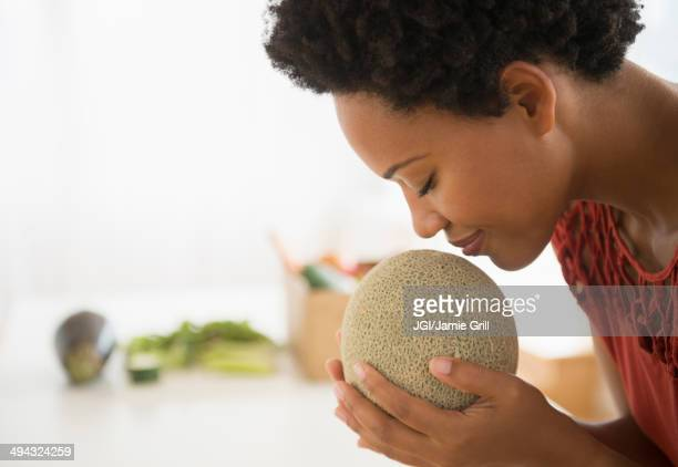 Black woman smelling cantaloupe