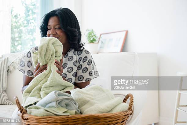 Black woman smelling clean laundry