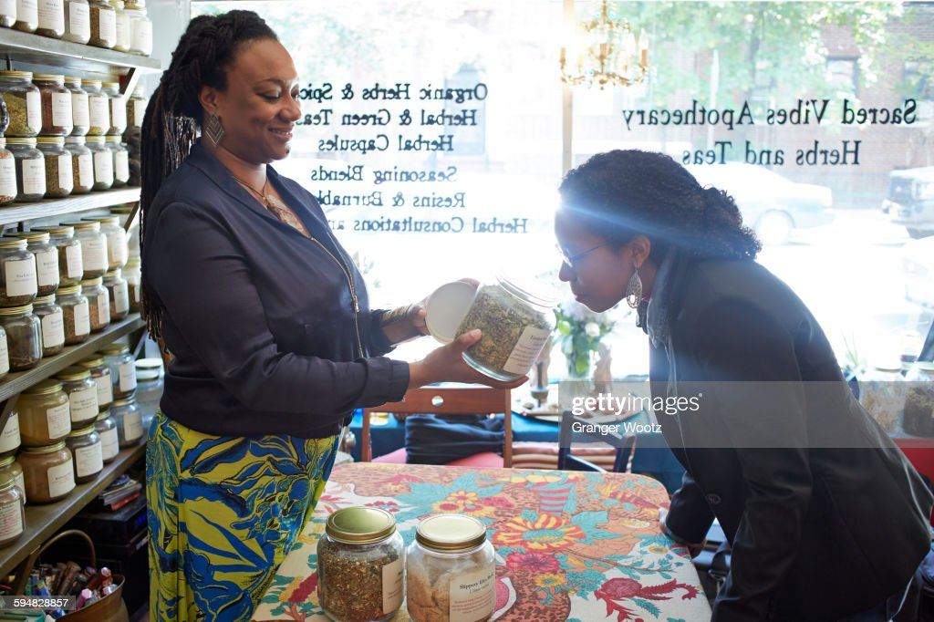 Black woman smelling tea in tea shop : Stock Photo