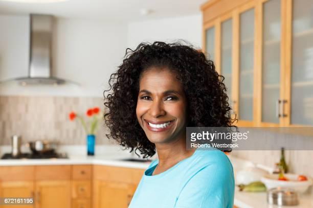 black woman smiling in kitchen - roberto ricciuti foto e immagini stock