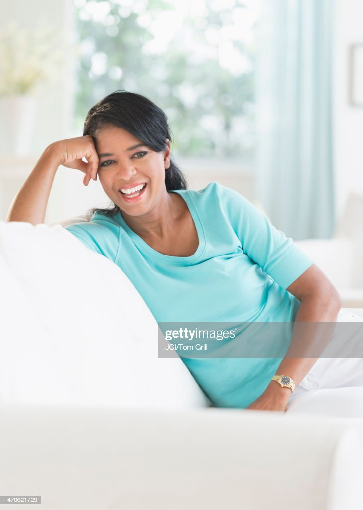 Black woman smiling on sofa : Stock Photo