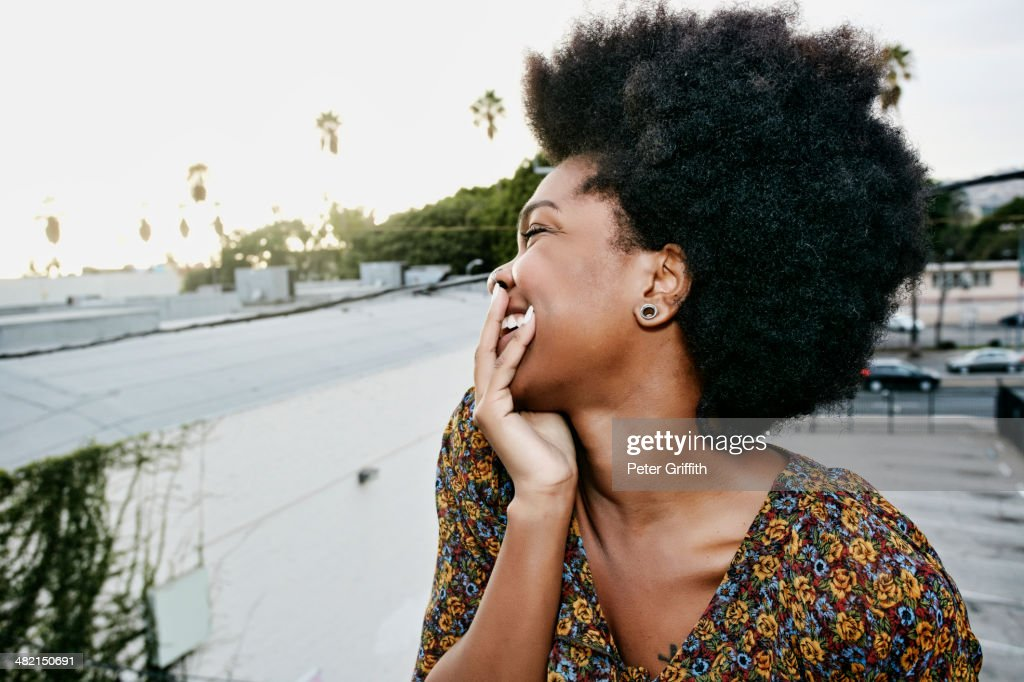 Black woman smiling on urban rooftop : Stock Photo