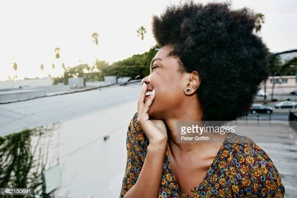 Black woman smiling on urban rooftop
